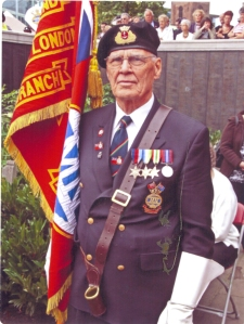 Ronald Quested stands proudly on parade with his Merchant Navy standard