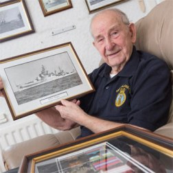 Ron Veitch holds a picture of HMS Glasgow